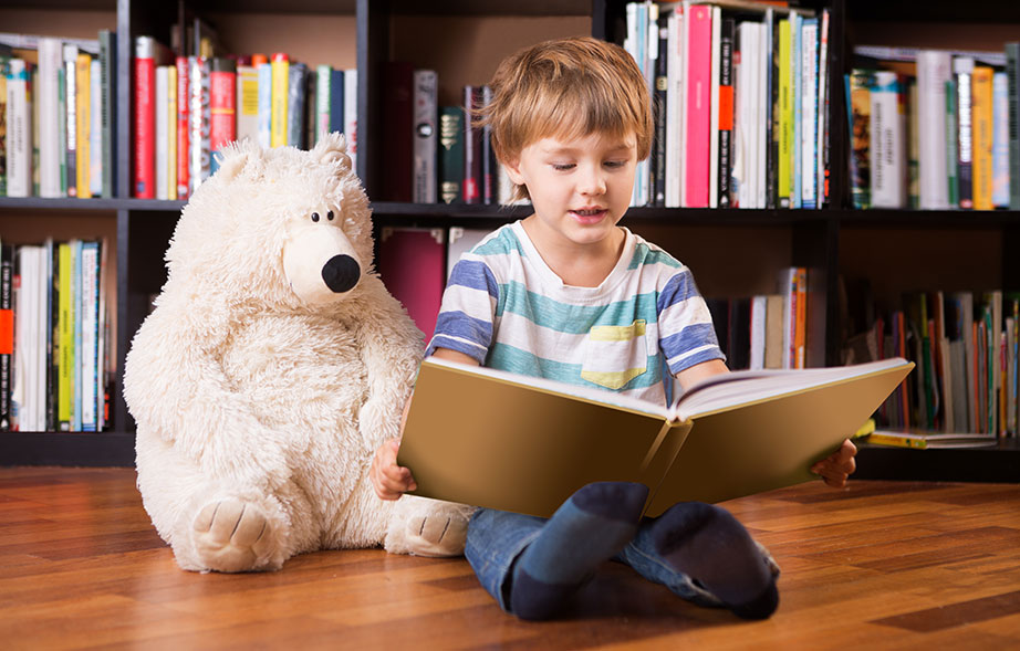 Toddler reading a book in the library