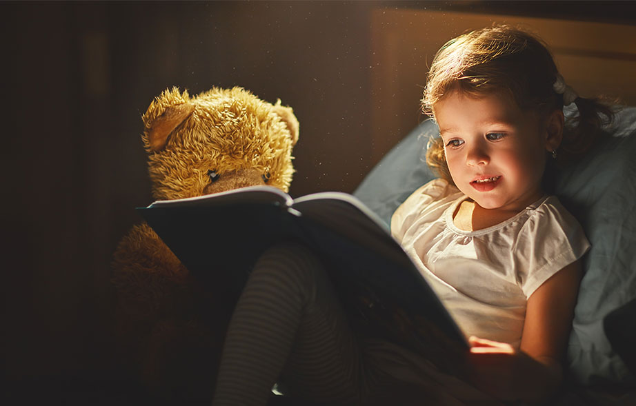 Toddler reading a book in bed